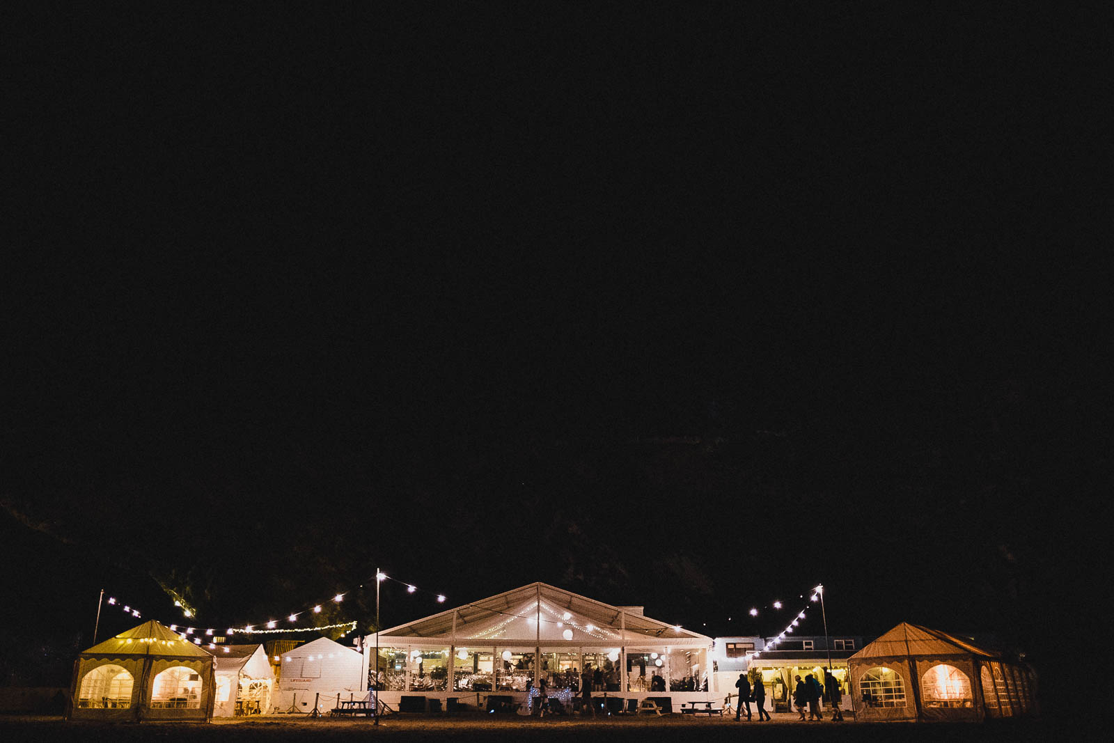 Lusty Glaze wedding venue at night, lit up by festoon lighting.