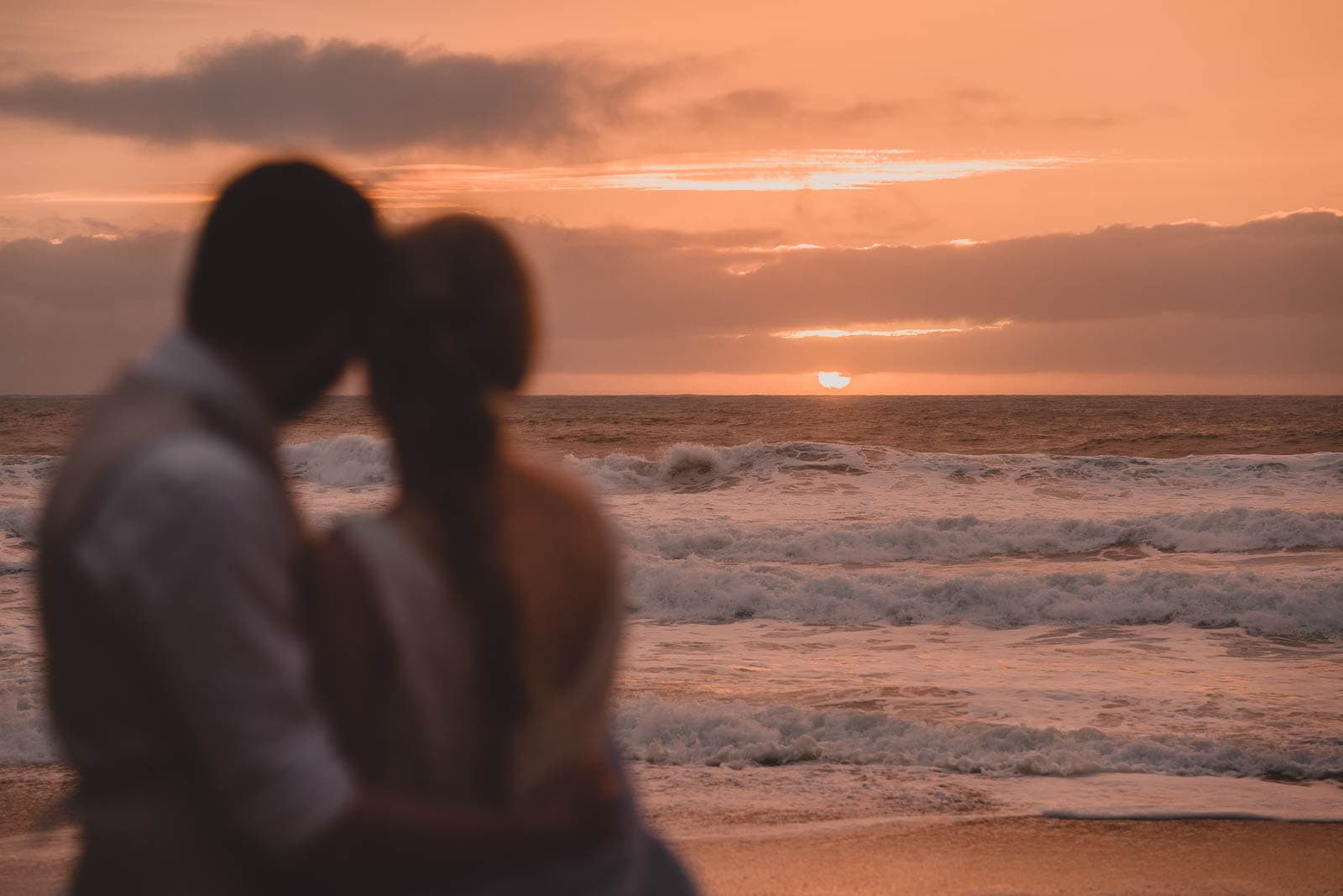 Lusty Glaze Wedding Photography. A stunning orange sunset at Lusty Glaze beach, with the bride and groom watching on.