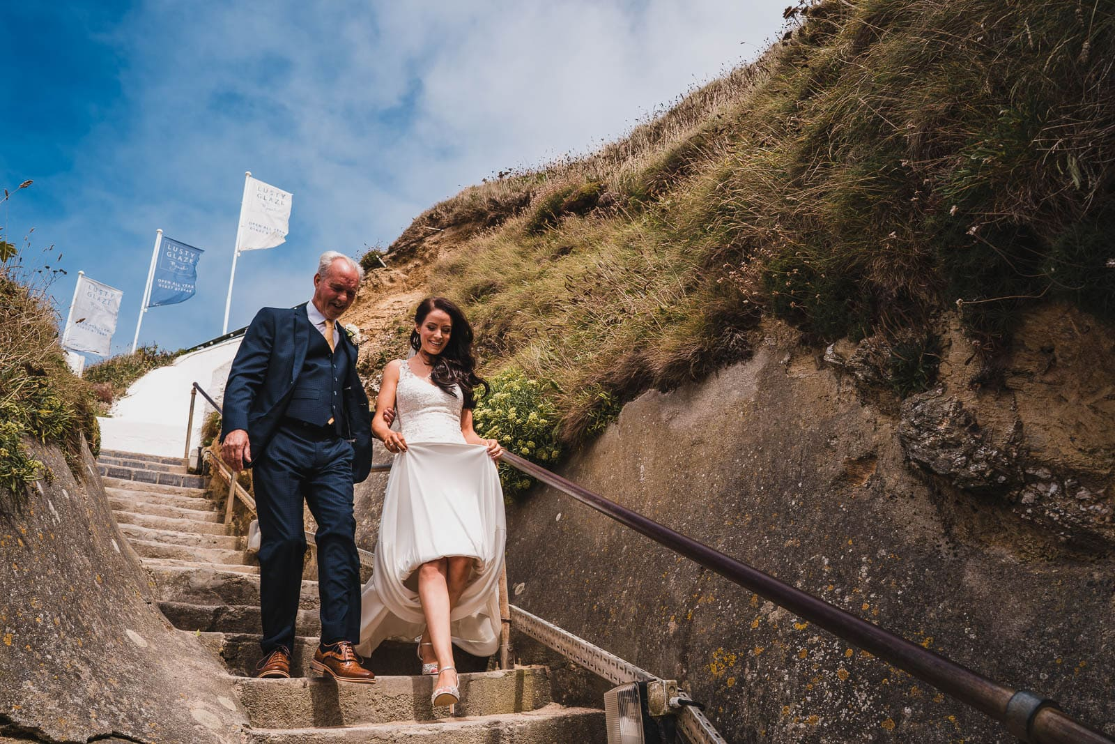 A bride and her Dad walk down the steps to Lusty Glaze beach for the wedding day.