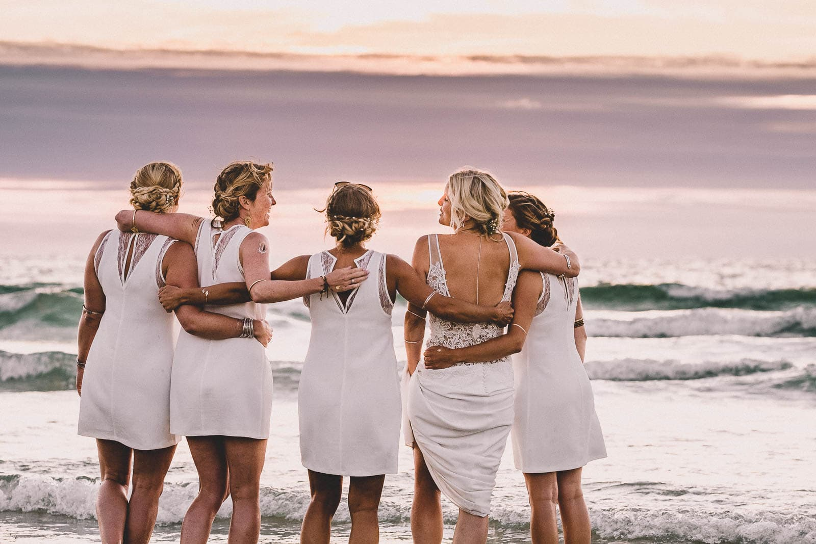 Lusty Glaze Wedding Photography. A bride and bridesmaids watch the sun setting on Lusty Glaze beach.