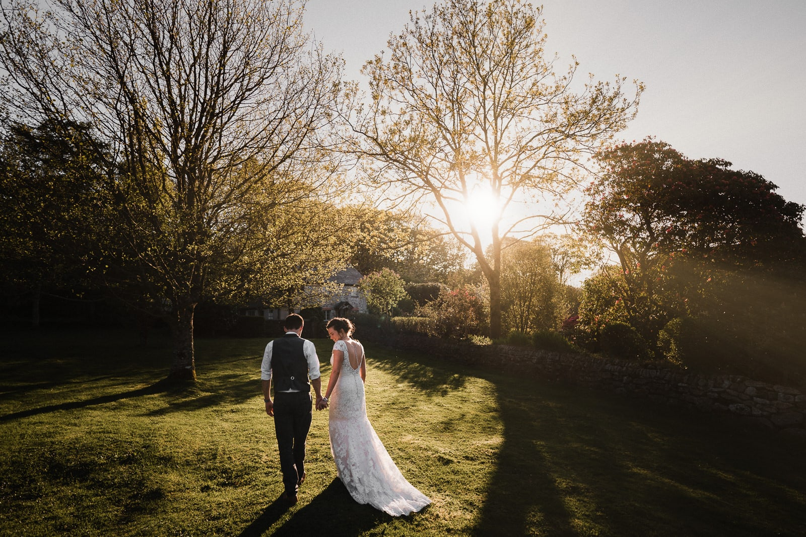 Bride and groom strolling hand in hand through the grounds of Cosawes Barton on their wedding day, while the sun sets through the trees