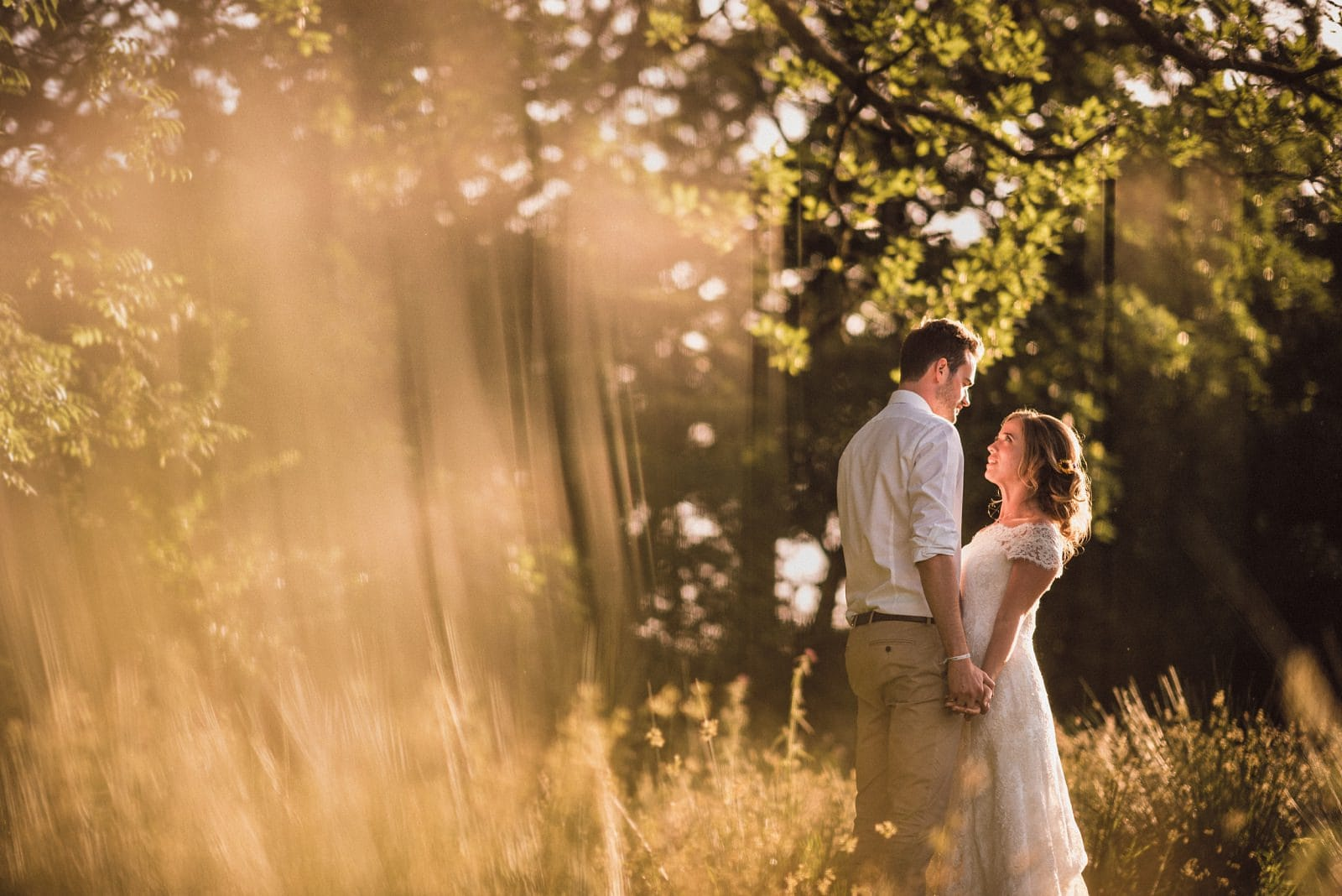 Wedding portrait at Nancarrow Farm with sunlight coming through trees and golden grass