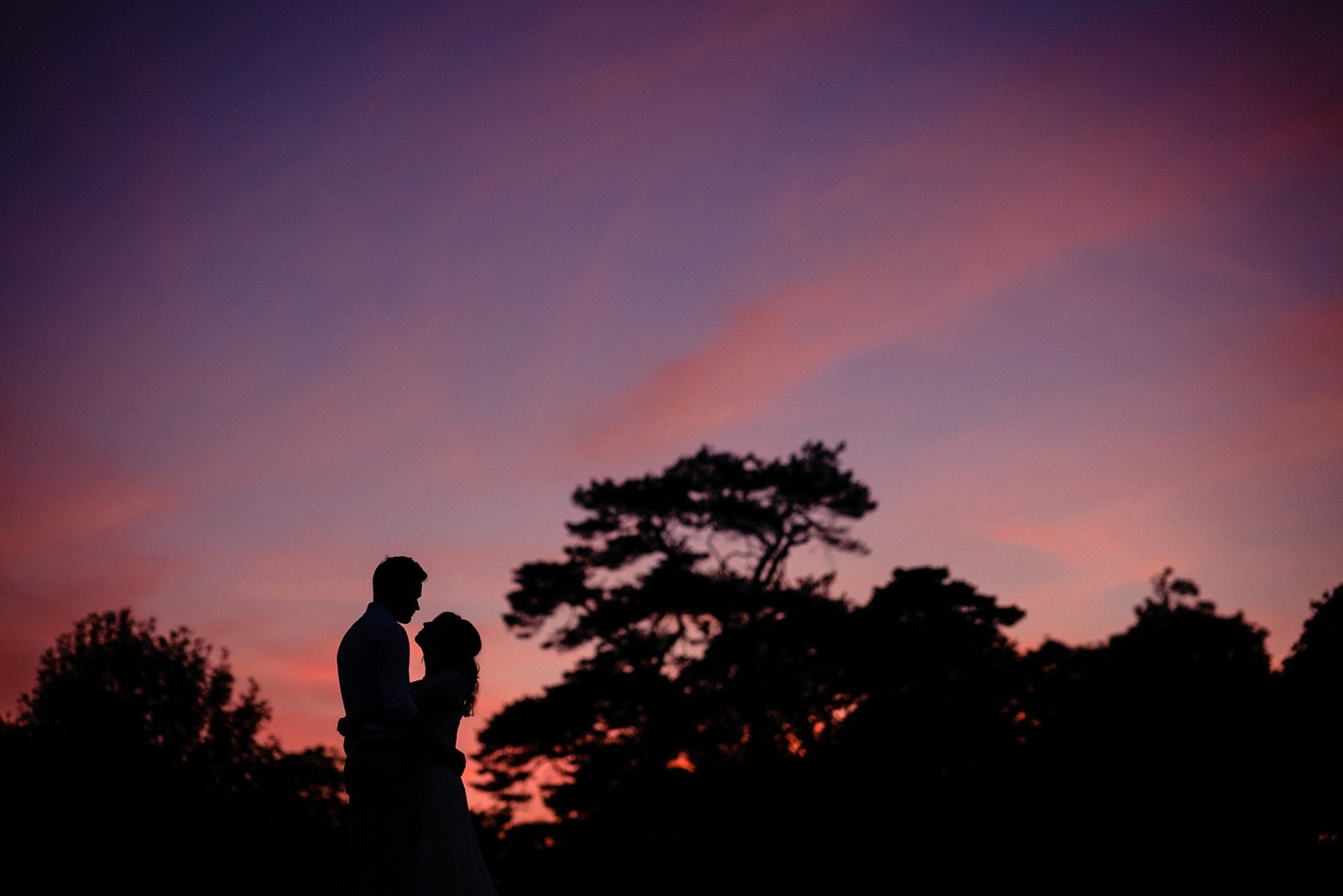 A bride and groom silhouetted against a purple sky at Nancarrow Farm