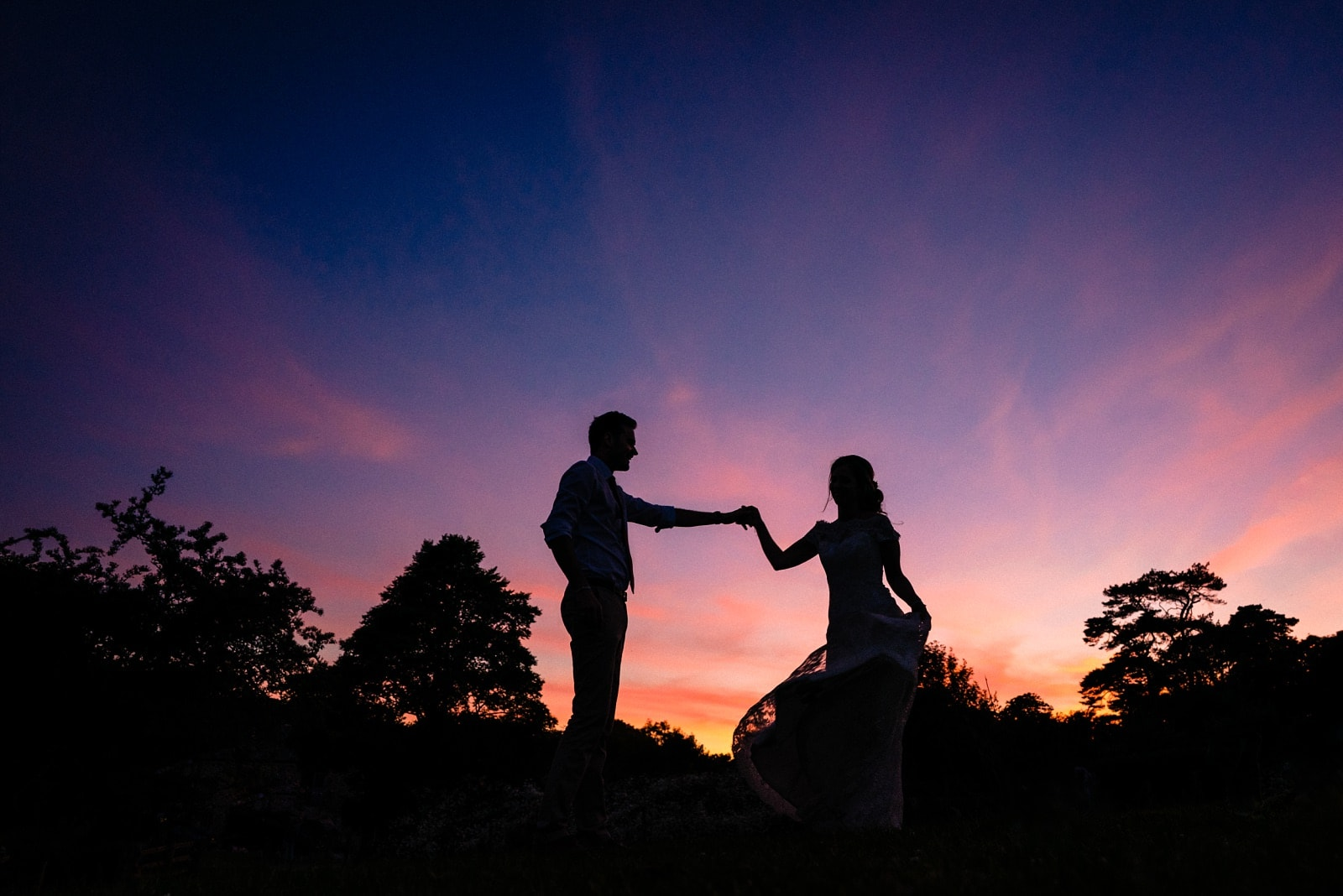 Silhouette of a bride and groom on their wedding day at Nancarrow Farm, in front of a purple sunset.