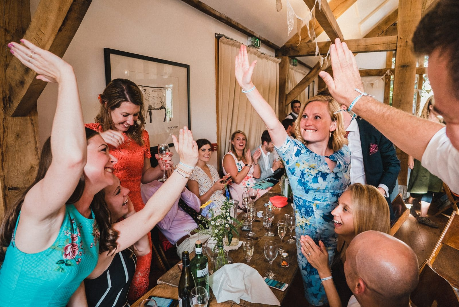 Wedding guests high five in the Oak Barn at Nancarrow