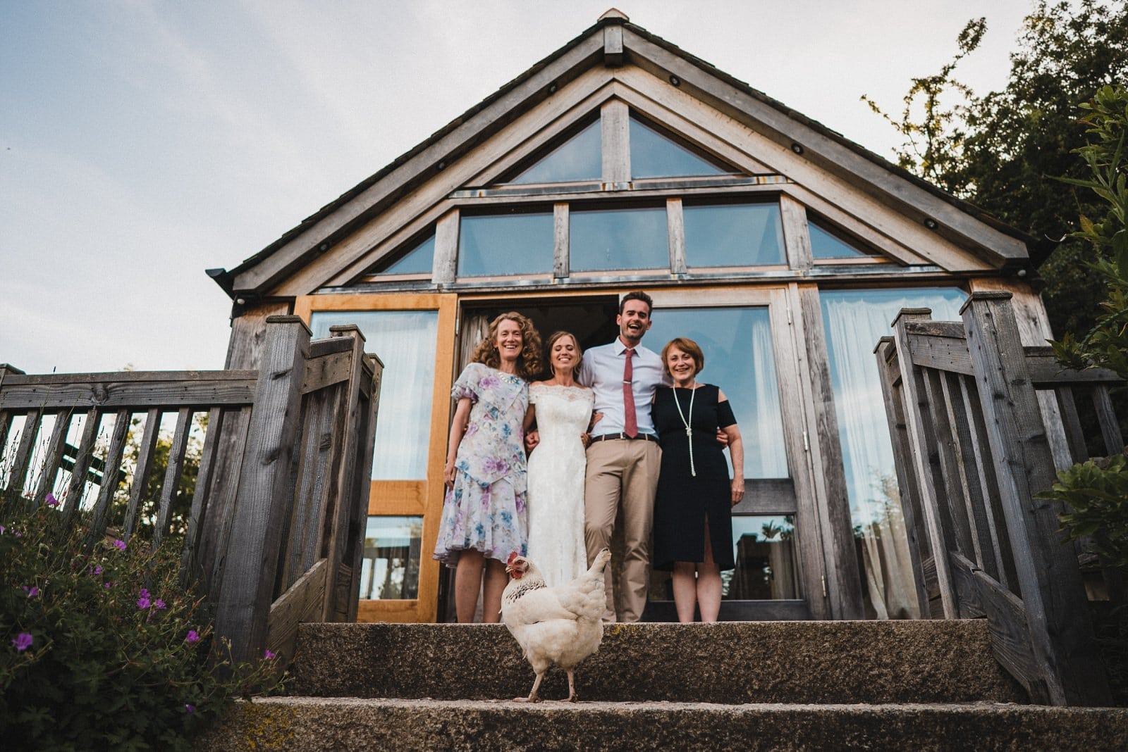 A wedding group photograph at Nancarrow Farm with a chicken stepping into the way