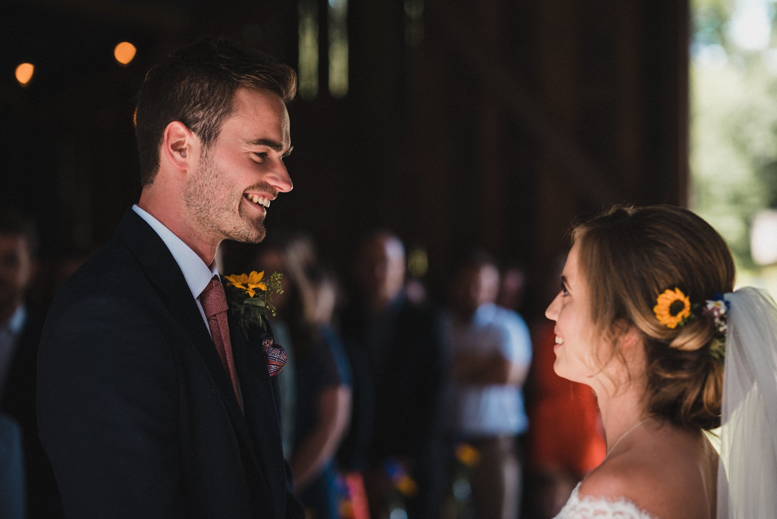 The groom smiling at his bride during the wedding vows at Nancarrow Farm's Rusty Barn
