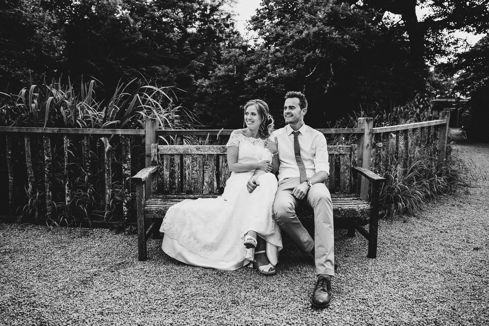 The bride and groom relaxing in front of the lake on their wedding day at Nancarrow Farm