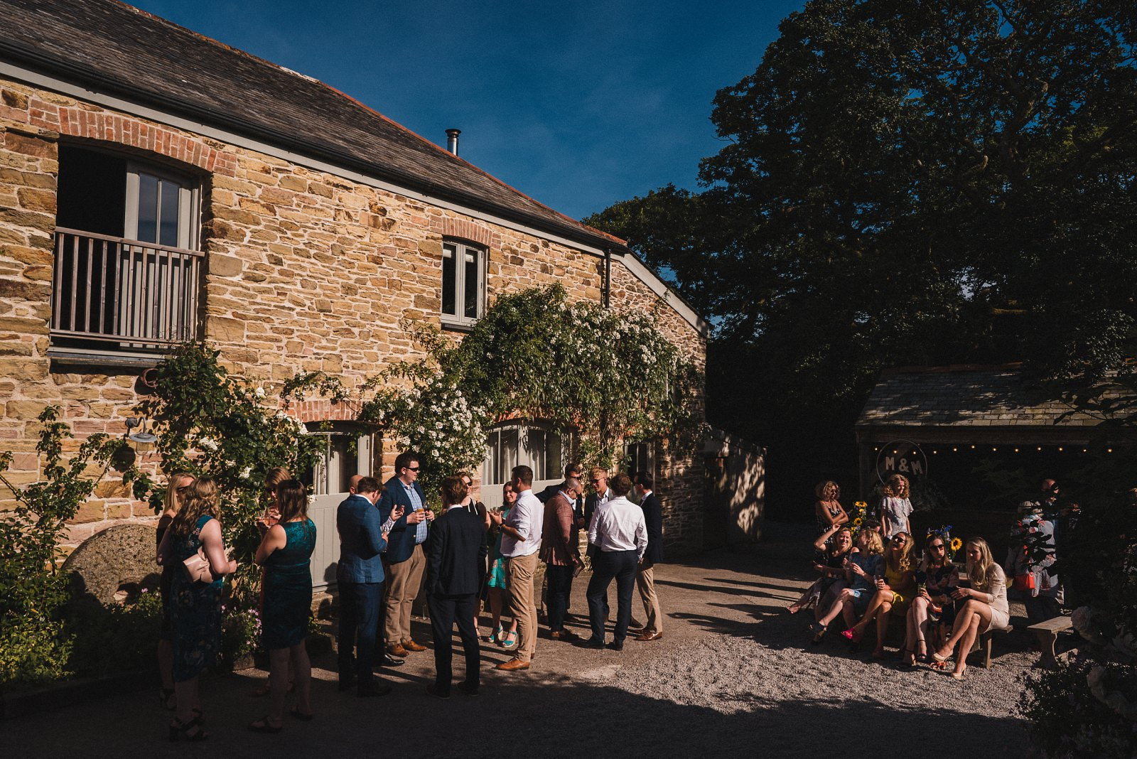 Wedding guests enjoying the sun in the courtyard at Nancarrow Farm