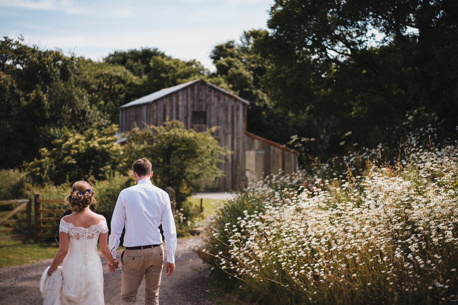 The bride and groom walk towards the Rusty Barn at Nancarrow Farm on their wedding day