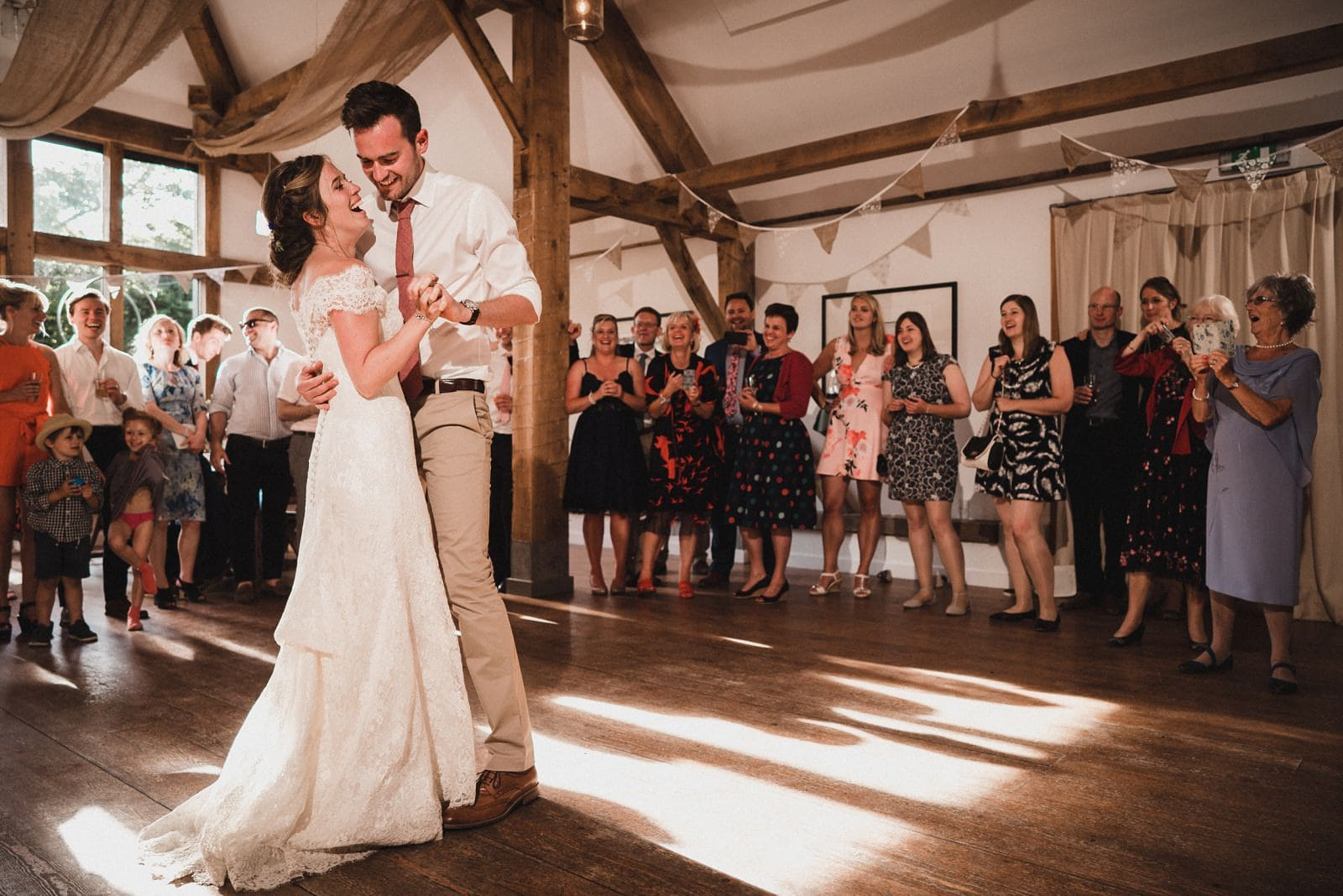 The first dance at Nancarrow Farm, with the couple laughing and guests looking on