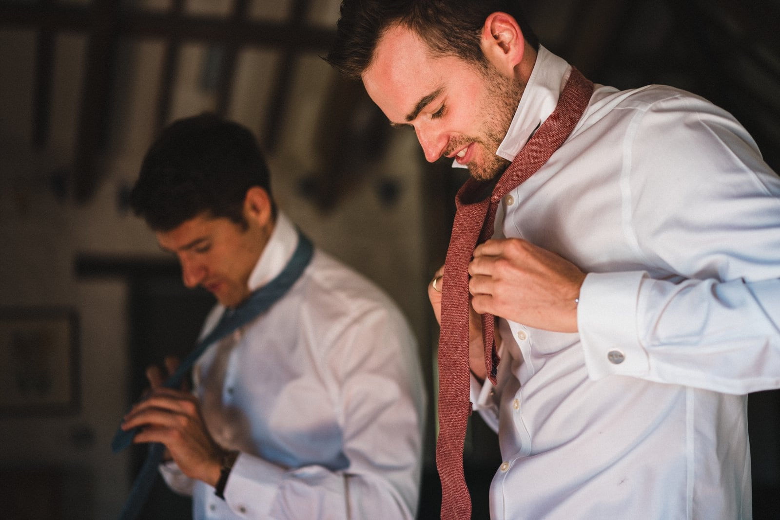 A groom putting his tie on at Nancarrow Farm on his wedding day
