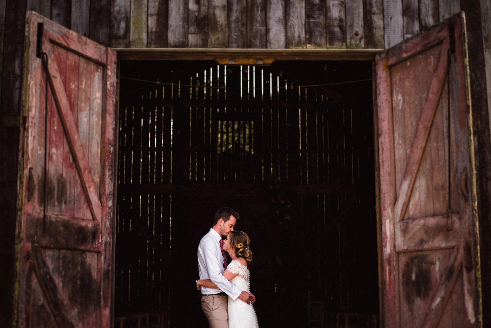 The couple hug in the Rusty Barn at Nancarrow Farm on their wedding day