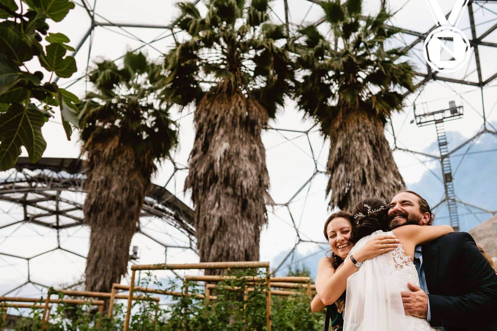 A wedding image at the Eden Project of a bride and two guests embracing infront of some huge trees.