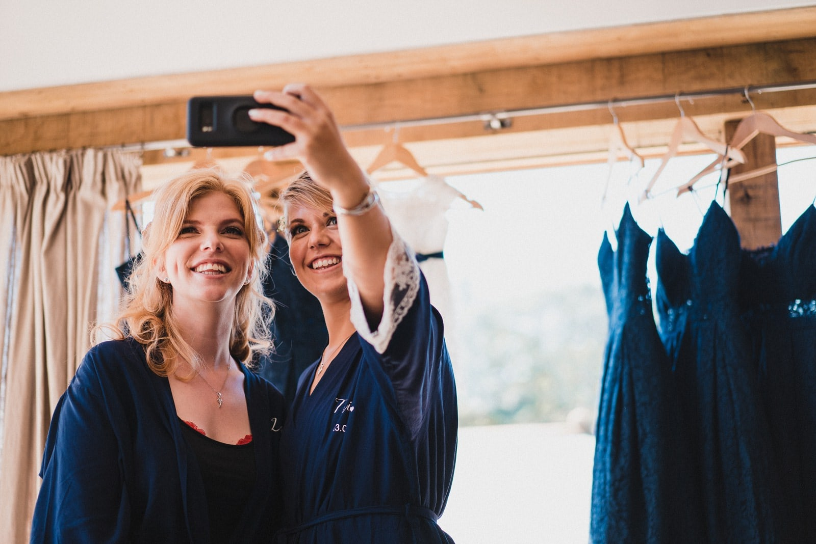 Two bridesmaids taking a selfie while getting ready for the wedding day