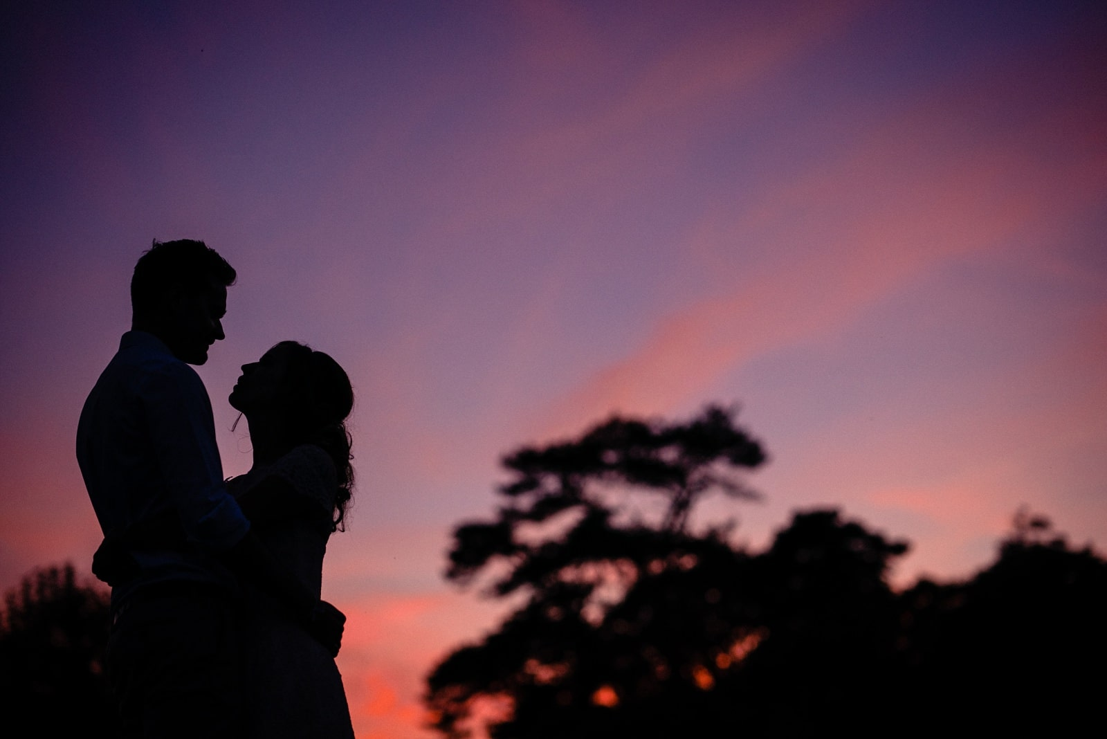 The bride and groom silhouetted against a purple sky at Nancarrow Farm