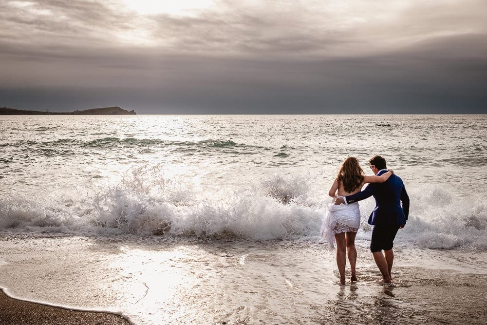 Wedding Photograph of a couple in front of a breaking wave